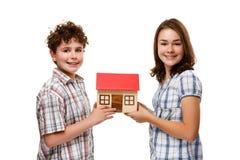Crianças que mantêm o modelo da casa isolado no branco Foto de Stock