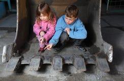Crianças que sentam-se dentro da cubeta do trator Fotografia de Stock Royalty Free