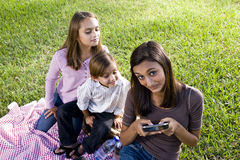 Crianças que têm o piquenique no parque que joga com smartp Imagem de Stock Royalty Free