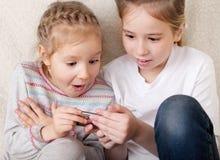 Crianças surpreendidas com telefone móvel Fotografia de Stock Royalty Free