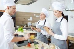 Criando o menu na cozinha do restaurante fotografia de stock