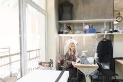 Criando a roupa à moda costureira bonito no local de trabalho em um estúdio moderno brilhante foto de stock royalty free
