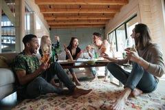 Criant cinq amis s'asseyant la maison et en mangeant de la pizza Photos libres de droits