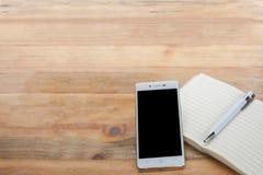 Criativo com caderno, telefone celular e pena no assoalho de madeira Fotografia de Stock Royalty Free