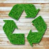 Recicl o símbolo da grama no fundo de madeira Fotos de Stock Royalty Free