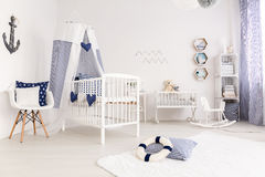 Crib with canopy. White crib with canopy in marine style interior royalty free stock images