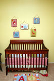 Crib in Nursery. A brown crib sits up against a yellow wall in a baby's nursery with various decorations on the wall Royalty Free Stock Photo