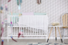 Crib with pillows. White crib with pastel pillows against wall in modern baby room stock image