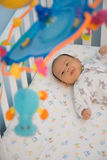 Crib time. 3 Month Old baby in baby crib staring at mobile Royalty Free Stock Images