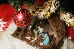 Crib under the tree. View of a crib under a christmas tree with decoration Stock Photos
