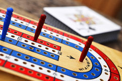 Cribbage board and playing cards Stock Images