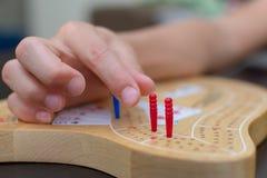 Cribbagekaartspel en raad omhoog het dichte bekijken de blauwe en rode pinnen royalty-vrije stock afbeeldingen