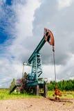 Cric de pompe à huile dans le domaine en Russie sous les cieux nuageux Photo stock