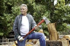 Cric supérieur de bois de charpente tenant une hache et regardant loin Photos stock