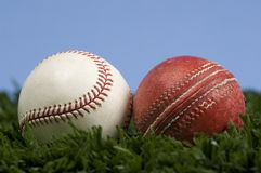 Cricket ball and Baseball. On grass with blue sky - illustration of the way things change. Baseball is an evolution of cricket stock photography