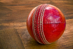 Cricket ball on wooden bat. Close up of cricket ball on wooden bat stock images