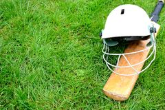 Cricket bat and helmet. On grass Royalty Free Stock Photo