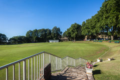 Cricket Field Oval Game. Scenic Cricket field oval grounds pitch cut rolled and marked white batting bowling creases with wickets and bails ready for game stock images