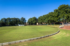 Cricket Field Oval Game. Cricket field oval grounds pitch cut rolled and marked white batting bowling creases with wickets and bails ready for game royalty free stock photo