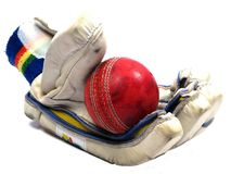 Cricket glove holding red ball Stock Images