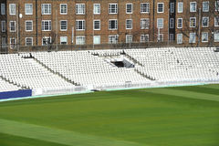 Cricket ground. Empty white stadium seating at cricket ground with grass in forground Stock Photos