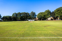 Cricket Pitch Wickets Game. Cricket grounds pitch cut rolled and marked white batting bowling creases with wickets and bails ready for game stock image