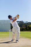 Cricket player batting on field against sky. Full length of cricket player batting on field against clear sky Stock Image