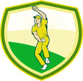 Cricket Player Bowling Crest Cartoon. Illustration of a cricket player fast bowler bowling with cricket ball set inside shield crest viewed from front done in Royalty Free Stock Photo
