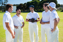 Cricket players standing at field. Against clear sky stock image