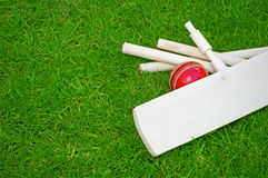 Cricket set. Including ball, bat and stumps on green grass pitch with copy space Stock Photo