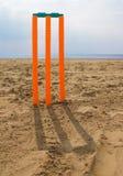 Cricket stumps on beach. Bright orange toy cricket stumps on beach with shadow approaching viewer Royalty Free Stock Images