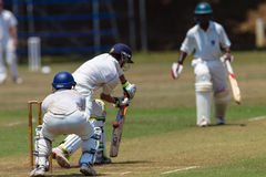 Cricket Summer High Schools Game. 1st Team High school batsman plays a defensive stroke and his playing partner watches on as the wicketkeeper stands poised Stock Images