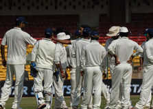 Cricket team group. Rest of India players get together after a wicket falls in their Irani Cup game against Karnataka stock images