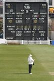 Cricket umpire and scoreboard. Scene at first class English cricket match Royalty Free Stock Photos