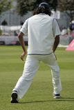 Cricketer stretching. Warming up in the field before start of play royalty free stock images