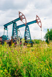 Crics de pompe à huile dans le domaine en Russie sous les cieux nuageux Photographie stock