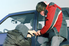 Crime. Two crime guys breaking car door Royalty Free Stock Images