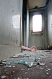 Crime. A person lying in doorway unconscious in messy environment Royalty Free Stock Photos