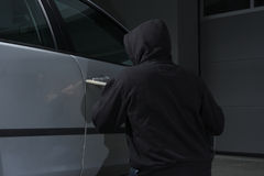 Crime. Criminal car theft thief stealing breaking a car in the dark Stock Photos