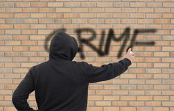 CRIME. Person spraying crime on a wall Royalty Free Stock Photos