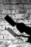 Crime Concept. Hand holding an axe shaped knife in front of brick wall with harsh shaddow Stock Photography