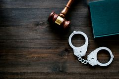 Crime concept. Metal handcuffs near judge gavel and law book on dark wooden background top view copy space. Crime concept. Metal handcuffs near judge gavel and stock photo