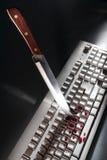 Crime de Cyber avec le clavier d'ordinateur poignardant de couteau Images stock