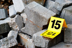 Crime Evidence Marker Next to Concrete. Real police crime scene evidence markers stock photo