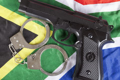 Crime and justice concept with handgun on a South African flag. Crime and justice concept with handgun on South African flag Stock Photos
