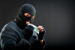 Crime man biting euro Stock Images