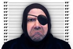 Crime man. Portrait of a man with the eyepatch on background mugshot Royalty Free Stock Photo