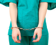 Crime in medicine. Lady doctor in green uniform with handcuffed hands, focus on foreground, white background Royalty Free Stock Photography