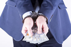 Crime and Money. Handcuffs are on the dollar. Photo showing money with handcuffs Stock Photography