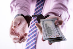 Crime and Money. Handcuffs are on the dollar. Photo showing money with handcuffs Stock Images